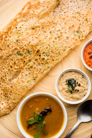 Onion rava masala dosa is a South Indian instant breakfast served with chutney and sambar over moody background. selective focus