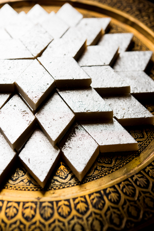 Kaju Katli is a Diamond shape Indian sweet made using cashew sugar and mava, served in a plate or bowl over moody background. selective focus