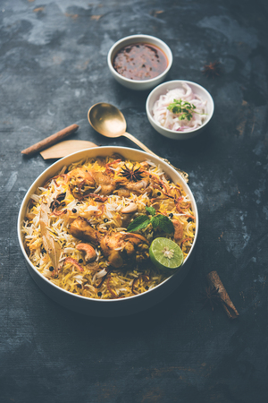 Delicious spicy chicken biryani in bowl over moody background, it's a popular Indian and Pakistani food.