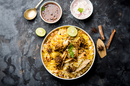 mutton or lamb biriyani with basmati rice, served in a bowl over moody background. Banco de Imagens