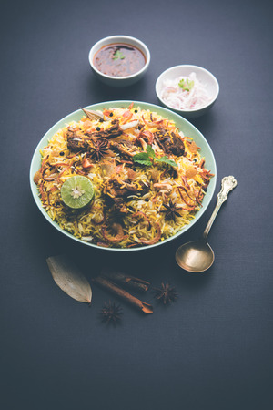 mutton or lamb biriyani with basmati rice, served in a bowl over moody background. Imagens
