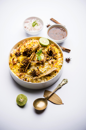 mutton or lamb biriyani with basmati rice, served in a bowl over moody background. Stock fotó