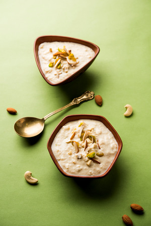 Sweet Rabdi or Lachha Rabri or basundi, made with pure milk garnished with dry fruits. Served in a bowl over moody background. Selective focus 免版税图像