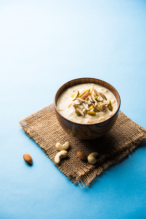 Sweet Rabdi or Lachha Rabri or basundi, made with pure milk garnished with dry fruits. Served in a bowl over moody background. Selective focus Imagens