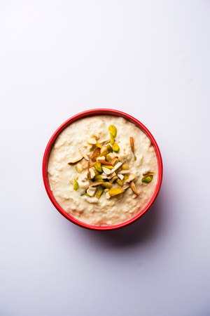 Sweet Rabdi or Lachha Rabri or basundi, made with pure milk garnished with dry fruits. Served in a bowl over moody background. Selective focus Фото со стока