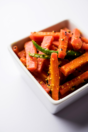 Carrot Pickle / Gajar ka Achar or Loncha in hindi. Served in a bowl over moody background. Selective focus 스톡 콘텐츠