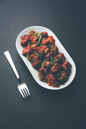 Indian Chilli Chicken dry, served in a plate over moody background. Selective focus 스톡 콘텐츠