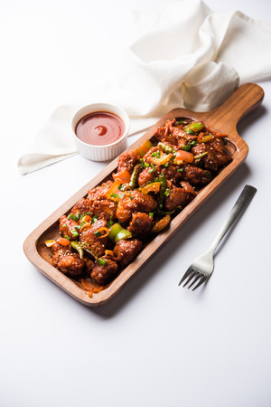 Indian Chilli Chicken dry, served in a plate over moody background. Selective focus Stock Photo