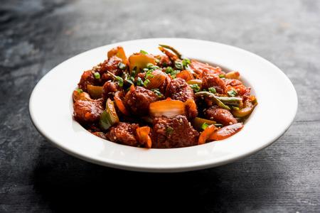 Pollo con chile indio seco, servido en un plato sobre fondo cambiante. Enfoque selectivo