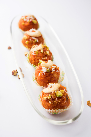 Carrot Halwa Laddu or sweet balls,  served in a plate with dry fruits toppings. selective focus