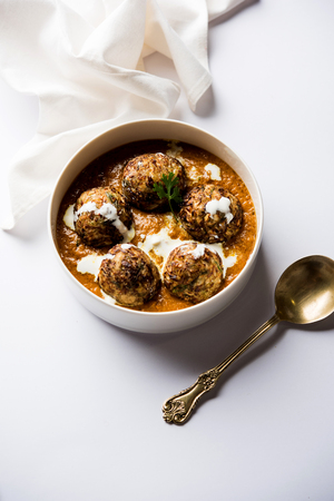 Malai Kofta is a Mughlai Speciality dish served in a bowl or pan over moody background. selective focus