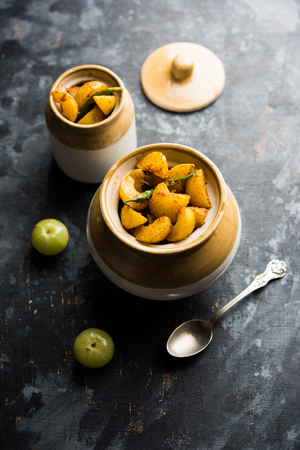 Homemade Gooseberry or amla Pickle/ or Aavle ka Achar in a bowl or barni over moody background.  selective focus Stockfoto
