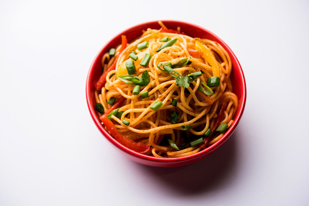 Schezwan Noodles or vegetable Hakka Noodles or chow mein is a popular Indo-Chinese recipes, served in a bowl or plate with wooden chopsticks. selective focus