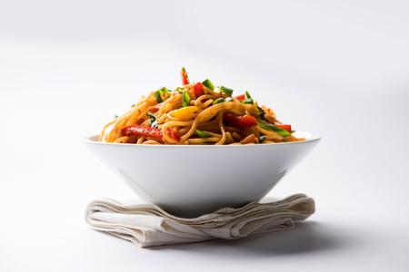 Los fideos Schezwan o los fideos Hakka de verduras o chow mein son recetas populares indochinas, que se sirven en un tazón o plato con palillos de madera. enfoque selectivo