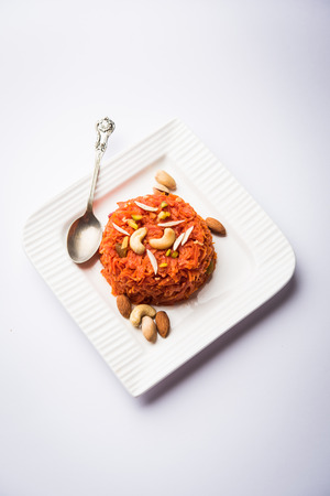 Gajar ka halwa is a carrot-based sweet dessert pudding from India. Garnished with Cashew/almond nuts. served in a bowl.