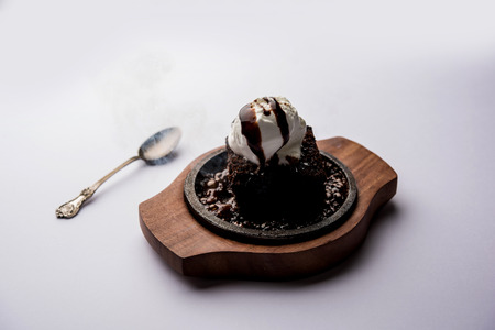 sizzling chocolate brownie is a sweet dish made using scoop of ice-cream on top served with a generous pouring of melted chocolate. server hot. selective focus