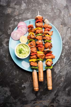 Chicken tikka /skew Kebab. Traditional Indian dish cooked on charcoal and flame, seasoned & colourfully garnished. served with green chutney and salad. selective focus Stockfoto