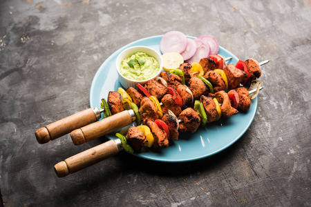 Chicken tikka /skew Kebab. Traditional Indian dish cooked on charcoal and flame, seasoned & colourfully garnished. served with green chutney and salad. selective focus Imagens - 113422723