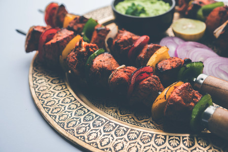 Chicken tikka /skew Kebab. Traditional Indian dish cooked on charcoal and flame, seasoned & colourfully garnished. served with green chutney and salad. selective focus 免版税图像