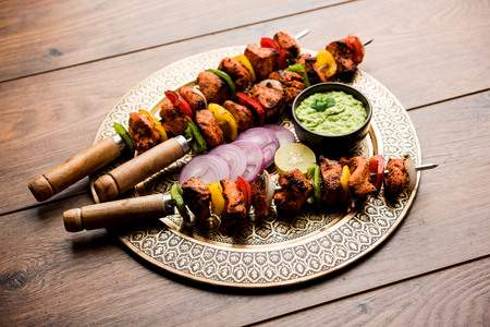 Chicken tikka /skew Kebab. Traditional Indian dish cooked on charcoal and flame, seasoned & colourfully garnished. served with green chutney and salad. selective focus Stock Photo