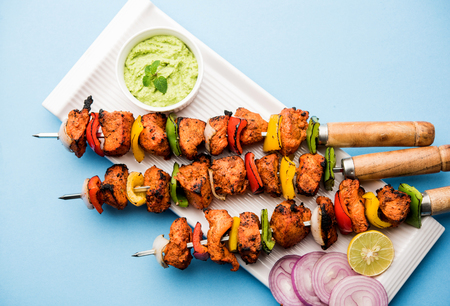 Chicken tikka /skew Kebab. Traditional Indian dish cooked on charcoal and flame, seasoned & colourfully garnished. served with green chutney and salad. selective focus