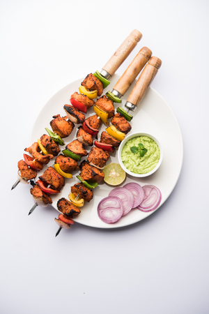 Indian chicken tikka kebabs, marinated in spices and yogurt and roasted in tandoor. served with green chutney and onion. selective focus Stock Photo