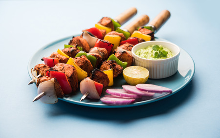 Chicken tikka skew Kebab. Traditional Indian dish cooked on charcoal and flame, seasoned & colourfully garnished. served with green chutney and salad. selective focus Stock Photo