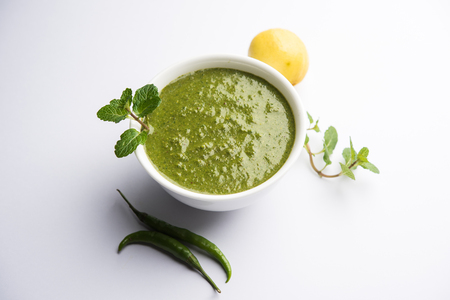 Healthy Green Mint Chutney Made with Coriander, pudina And Spices. isolated moody background. selective focus