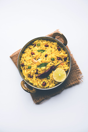 Lemon Rice is a South Indian turmeric rice or maharashtrian recipe called fodnicha bhat using leftover rice garnished with nuts curry leaves and lemon juice, selective focus Reklamní fotografie