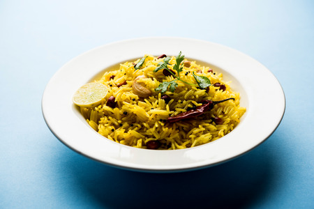 Lemon Rice is a South Indian turmeric rice or maharashtrian recipe called fodnicha bhat using leftover rice garnished with nuts curry leaves and lemon juice, selective focus 版權商用圖片