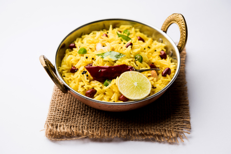 Lemon Rice is a South Indian turmeric rice or maharashtrian recipe called fodnicha bhat using leftover rice garnished with nuts curry leaves and lemon juice, selective focus Stock Photo