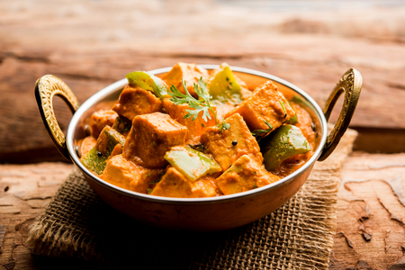 Malai or achari Paneer in a gravy made using red gravy and green capsicum. served in a bowl. selective focus Stock Photo