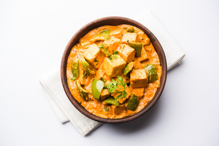 Malai or achari Paneer in a gravy made using red gravy and green capsicum. served in a bowl. selective focus Фото со стока