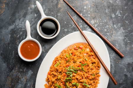 Schezwan Fried Rice Masala is a popular indo-chinese food served in a plate or bowl with chopsticks. selective focus