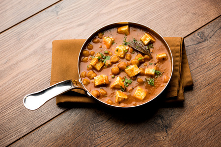 Chole Paneer curry made using boiled chickpea with cottage cheese with spices. Popular North Indian recipe. served in a bowl or serving pan. Selective focus Stock Photo
