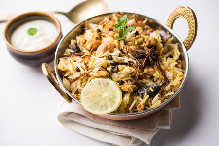 Keema or Kheema Biryani - Fragrant and spicy minced lamb or goat or chicken cooked in range of aromatic spices with basmati rice. served in a karahi with curd. selective focus