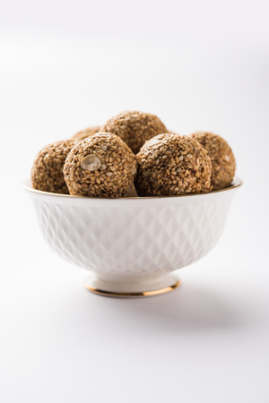 Tilgul Laddu or Til Gul balls for makar sankranti, it's a healthy food made using sesame, crushed peanuts and jaggery. served in a bowl. selective focus showing details. 版權商用圖片