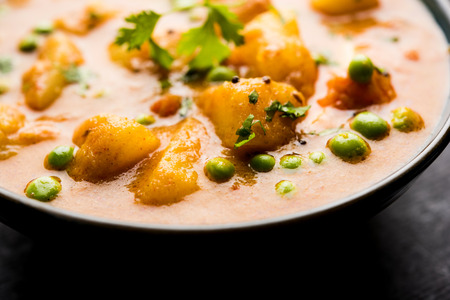 Indian Aloo Mutter curry - Potato and Peas immersed in an Onion Tomato Gravy and garnished with coriander leaves. Served in a Karahi/kadhai or pan or bowl. selective focus