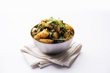 Aloo Palak sabzi - Potato cooked with spinach with added spices. a healthy Indian main course recipe. Served in a bowl, selective focus Banque d'images - 114531455