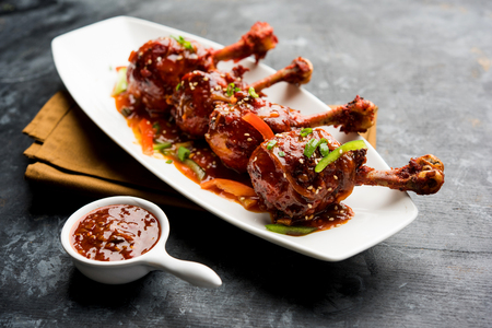 Szechuan Chicken which is a popular Indo-Chinese non vegetarian recipe. served in a plate with chilli sauce. selective focus Stockfoto
