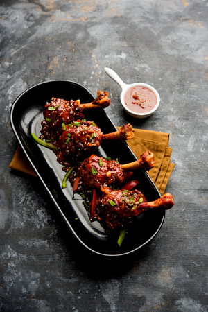 Szechuan Chicken which is a popular Indo-Chinese non vegetarian recipe. served in a plate with chilli sauce. selective focus Stock Photo