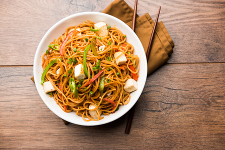 Schezwan hakka noodles with paneer or cottage cheese. Served in a bowl. selective focus