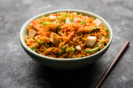 Schezwan paneer fried rice with Szechuan sauce and cottage cheese cubes. served in a bowl or plate or pan. selective focus