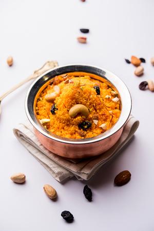 Badaam kesar shira / Sheera or almond saffron halwa, popular Indian dessert served in a bowl. selective focus