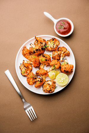 Tandoori Gobi / Roasted cauliflower Tikka is a dry dish made by roasting Cauliflowers in Oven/Tandoor. It's  popular starter food from India. served with ketchup. selective focus 免版税图像 - 116175735