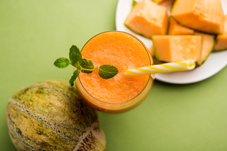 Musk melon juice with slice, also known as Kharbuj/kharbuja fruit extract, served in a glass with mint. selective focus