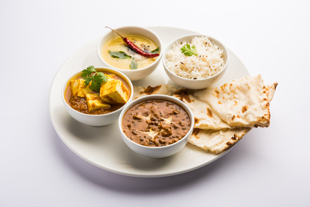 Indian vegetarian  platter / Thali having Palak paneer butter masala, dal makhani, flat bread or naan and rice served in a white plate