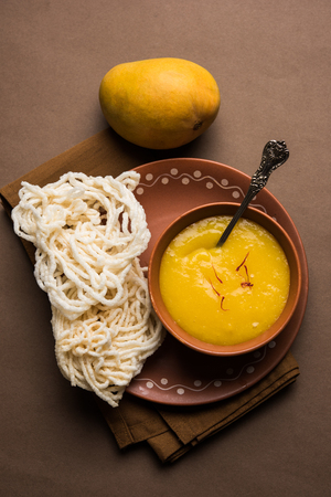 Aam Ras or Alphonso mango pulp with kurdai which is a fried dish made using wheat/gehu. selective focus