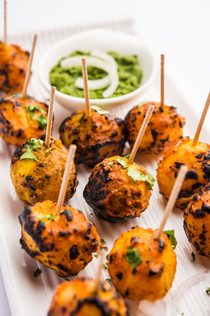 Tandoori aloo are roasted potatoes with Indian spices. It's a party appetizer served with green chutney. selective focus Reklamní fotografie