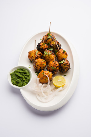 Tandoori aloo are roasted potatoes with Indian spices. It's a party appetizer served with green chutney. selective focus 免版税图像